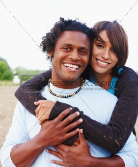 Happy young man carrying a laughing woman on his back