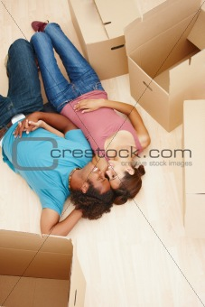 Smiling couple relaxing by boxes in their new house