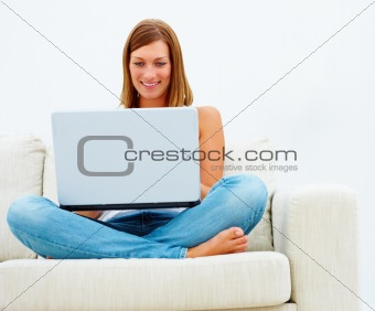 Woman sitting on sofa and using laptop