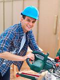 Closeup of a young man using an electric saw
