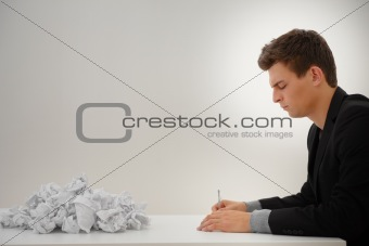 Profile of a business man writing by heap of papers
