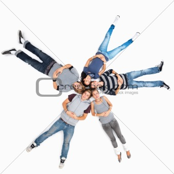 Young friends lying isolated together on white floor