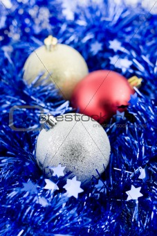 christmas colored balls in blue tinsel vertical orientation soft