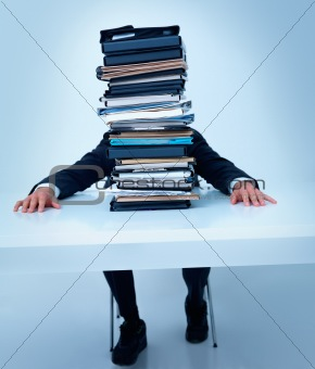 Man sitting at table with stack of files