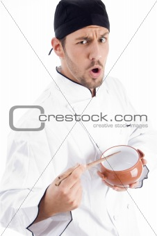 young chef holding bowl and chopstick and looking at camera
