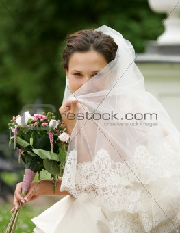 Bride hiding behind her veil