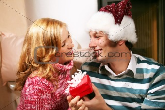 a couple in christmas time - he is holding a gift