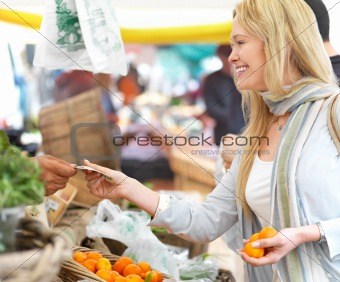 Happy blond woman buying food at market.