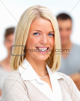 Smiling young office worker standing with people in background