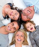 Happy family lying in a circle on white floor