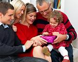 Happy family sitting togetheropening christmas presents