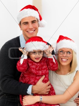 Festive young couple holding their daughter at christmas