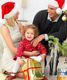 Smiling couple with a small child celebrating Christmas
