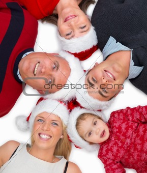 Family wearing Christmas hats and lying on floor in a circle