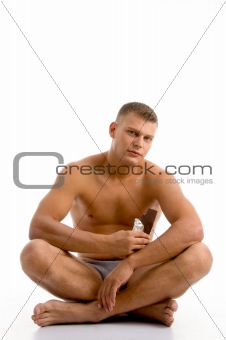 sitting muscular guy with chocolate