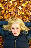 Woman lying on fall leaves with copyspace