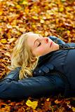 Woman lying on fallen leaves with eyes closed
