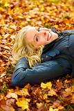 Smiling girl lying on fallen leaves looking at copyspace