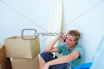 Surfer sitting in corner of room and talking on cellphone