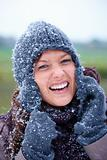 Smiling woman wearing woolen gloves and cap 