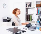 Young woman at work in office using computer 