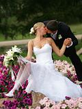 Newlywed couple kissing on flower bed