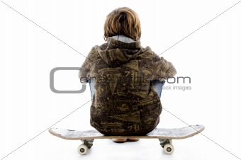 back pose of boy sitting on skateboard