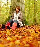 Autumn - Woman sitting under a tree