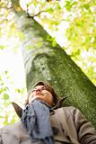 Low angle view of a woman standing against a tree