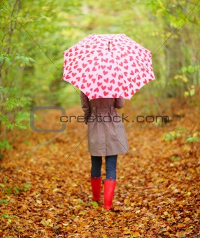 Back view of a woman walking with an umbrella