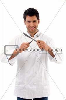 portrait of young male chef holding fork and knife