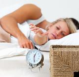 Beautiful woman on bed trying to hit alarm clock
