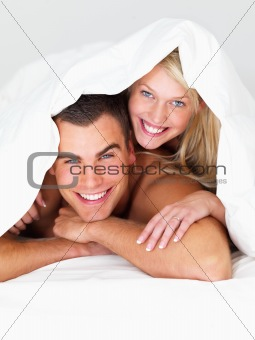 Young couple playing under the sheets