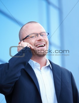 Happy businessman outside talking on cell