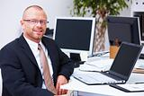 Relaxed business man sitting with laptop in office