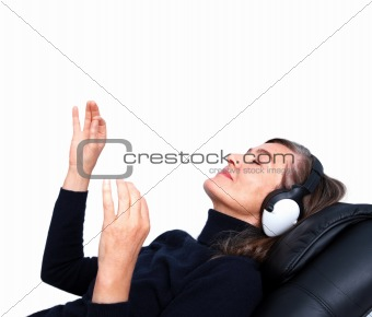 Happy senior woman lying in chair listening to music