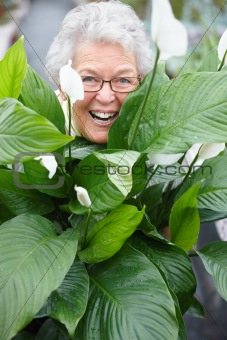 Older woman smiling happily behind a plant