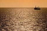 silhouette of fishing trawler at dusk