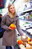 Smiling young woman buying produce in  a supermarket