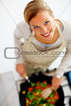 Top view of a young beautiful woman cooking food in kitchen