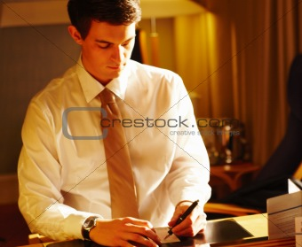 Portrait of a young businessman signing receipt