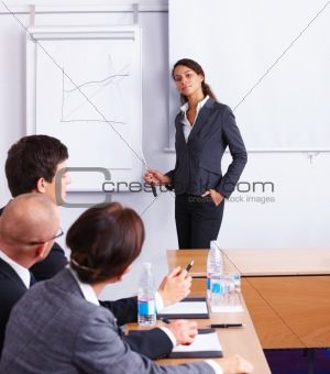 Friendly business woman explaining graph to colleagues in office