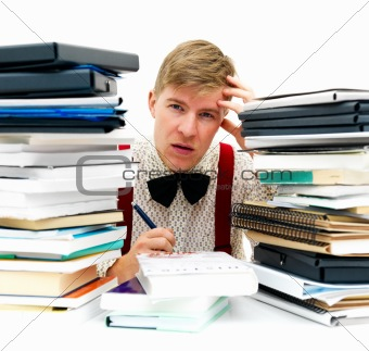 Overworked student sitting with stack of homework