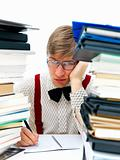 Bored student sitting with stack of extra work