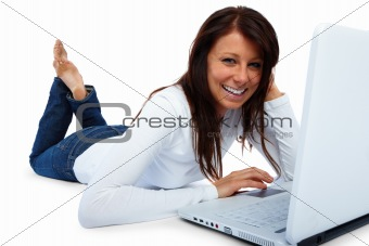 Happy  student lying and using laptop