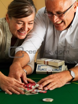 Successfull couple collecting gambling chips at casino
