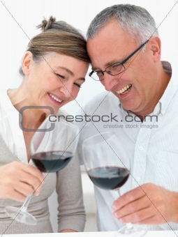 Mature joyful couple toasting wine