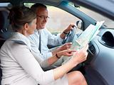 Travel - Happy couple looking at map in car
