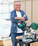 Handy man standing beside electric saw