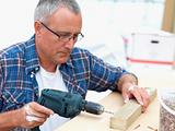 Mature carpenter drilling a hole in wood